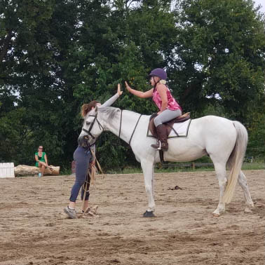 Ali McCool high-fiving her horse-riding student.